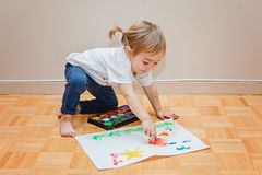 Fille d'enfant en bas âge essayant de dessiner avec son doigt Photographie stock libre de droits