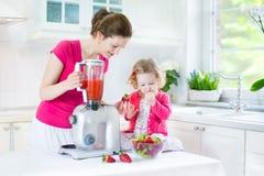 Fille d'enfant en bas âge et sa mère faisant la fraise fraîche photos libres de droits
