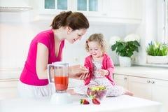 Fille d'enfant en bas âge et sa mère faisant la fraise fraîche photographie stock