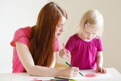 Fille d'enfant en bas âge et son dessin de maman avec des crayons Photographie stock libre de droits