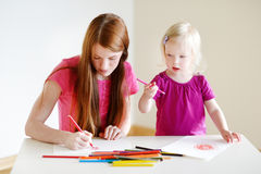 Fille d'enfant en bas âge et son dessin de maman avec des crayons Images libres de droits
