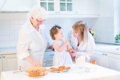 Fille d'enfant en bas âge faisant une tarte aux pommes cuire au four avec des grands-mères Photographie stock