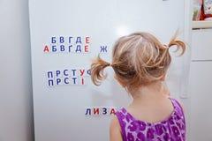 Fille d'enfant en bas âge jouant avec les lettres russes d'aimant sur le réfrigérateur Étude pour faire des mots Le relevé tôt Image stock
