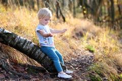 Fille d'enfant en bas âge jouant dans la forêt Photographie stock