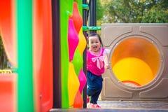 Fille d'enfant en bas âge jouant sur une glissière au terrain de jeu d'enfants Photos stock