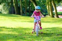 Fille d'enfant en bas âge montant son vélo image stock