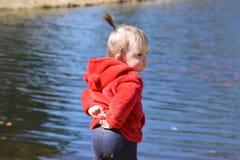 Fille d'enfant en bas âge se tenant devant l'étang Images stock