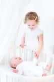 Fille d'enfant en bas âge tenant des mains avec le frère nouveau-né Photo stock
