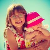 Fille d'enfant en bas âge tenant sa soeur le jour ensoleillé Photo libre de droits