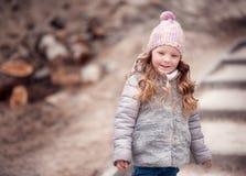 Fille d'enfant, habillée dans les supports chauds et le regard d'un manteau loin Image stock