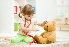 Fille d'enfant jouant le docteur et traitant le jouet de peluche Image libre de droits