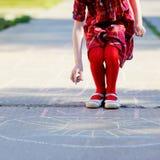 Fille d'enfant jouant le jeu de marelle sur l'asphalte Image stock