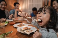 Fille d'enfant mangeant seule pendant le dîner photographie stock libre de droits