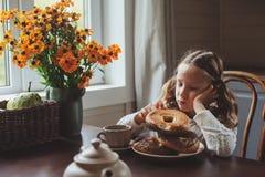 Fille d'enfant prenant le petit déjeuner à la maison dans le matin d'automne Intérieur moderne confortable de vie réelle dans la  Photo libre de droits