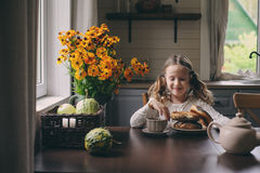 Fille d'enfant prenant le petit déjeuner à la maison dans le matin d'automne Intérieur moderne confortable de vie réelle dans la  Images libres de droits
