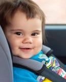 Fille d'enfant s'asseyant dans un siège de voiture de sécurité images stock