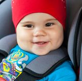 Fille d'enfant s'asseyant dans un siège de voiture de sécurité image stock