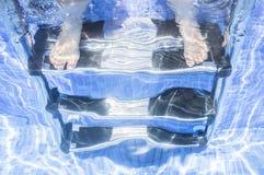 Fille d'enfant s'asseyant sur l'échelle de piscine avec l'underwa de jambes Photos stock