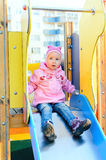 Fille d'enfant s'asseyant sur la glissière Images libres de droits