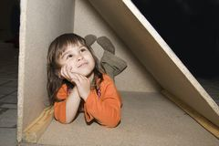 Fille d'enfant se cachant dans le cadre en bois, seuls rêves Image libre de droits