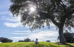 Fille d'enfant sous la nature enjoiying d'arbre de gland Photographie stock libre de droits