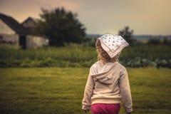 Fille d'enfant sur le champ rural examinant la distance sur le paysage rural dans la campagne pendant des vacances d'été symbolis Photo libre de droits