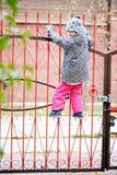 Fille d'enfant sur une barrière Images stock