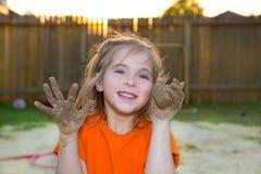 Fille d'enfants jouant avec la boule de sable de boue et les mains sales Photographie stock libre de droits