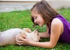 Fille d'enfants jouant avec le chien de chiwawa se trouvant sur la pelouse Photos stock