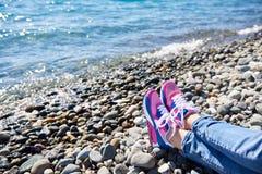 Fille d'espadrilles sur le fond de la mer et de la plage rocheuse Photos stock