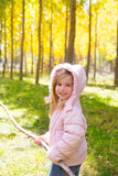Fille d'explorateur avec le bâton dans la forêt d'automne de jaune de peuplier Photos stock