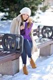 Fille d'hiver s'asseyant sur un banc parlant au téléphone Images stock