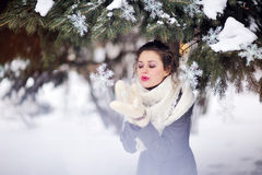 Fille d'hiver soufflant sur un flocon de neige dans des mitaines tricotées photos stock
