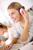 Fille d'étudiant dans la classe avec les écouteurs roses Photographie stock libre de droits
