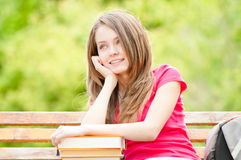Fille d'étudiant sur le banc avec des livres et rêver Images stock