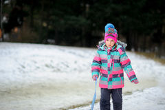 Fille d'un plus jeune âge scolaire sur la promenade en parc d'hiver au sujet de pente pour des toboggans Photo stock