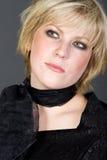 Fille d'une chevelure blonde courte mignonne contre le gris Photo libre de droits