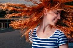 Fille d'une chevelure de gingembre secouant sa tête et long vol rouge de cheveux dans le ciel image libre de droits