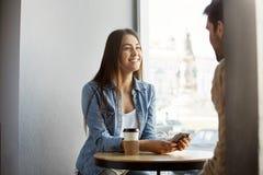 Fille d'une chevelure foncée joyeuse dans des vêtements élégants se reposant en cafétéria, café potable, riant et parlant avec l' Images stock