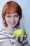 Fille d'une chevelure rouge avec la pomme verte images stock