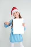 Fille d'ute de ¡ de Ð dans le chapeau de Santa Claus avec une feuille blanche de papier blanc ¡ De Ð Image stock