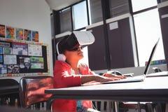Fille dactylographiant sur l'ordinateur portable tout en employant des écouteurs et des verres de réalité virtuelle images stock