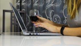 Fille dactylographiant sur un ordinateur portable et en même temps un vin rouge potable banque de vidéos