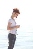 Fille dans des écouteurs à la plage Images libres de droits