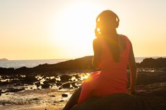 Fille dans des écouteurs écoutant la musique dans la ville au coucher du soleil photos libres de droits