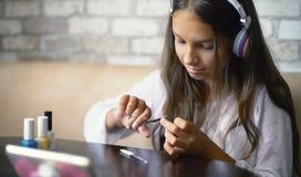 Fille dans des écouteurs causant en ligne au téléphone faisant des ongles de coupe de manucure avec l'espace gratuit et de copie photo libre de droits