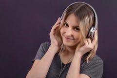 Fille dans des écouteurs souriant et écoutant la musique, génération z images stock