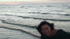 Fille dans des cheveux de secousse de robe à l'eau à la plage Photoshoot Sourire modèle pose banque de vidéos