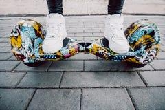 Fille dans des espadrilles blanches se tenant sur le scooter de compas gyroscopique Images stock