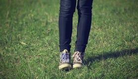 Fille dans des espadrilles de vintage se reposant sur l'herbe Photo libre de droits